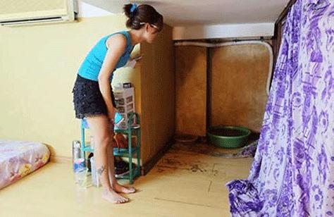 Chị Hoàng Phương Anh phải dùng hai chiếc thau để hứng, gom nước cống đen ngòm, hôi thối tràn ra nhà gần ba tháng nay. Ảnh: VH