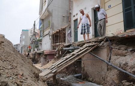Vỉa hè sát móng những ngôi nhà cao khiến người dân lo ngại tình trạng sụt lún nhà.