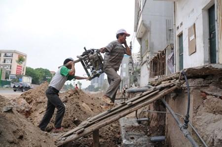 Các công nhân sửa nhà phải trèo chênh vênh bê máy móc.