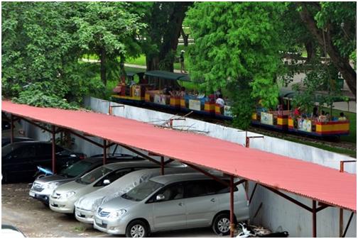 Những chiếc xe nối đuôi nhau đỗ ngoài trời trong khu đất trống của công viên Thống Nhất.