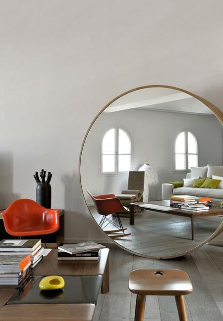 Chiếc gương tròn tạo nên hiệu quả bất ngờ cho căn phòng có những món đồ nội thất đơn giản.