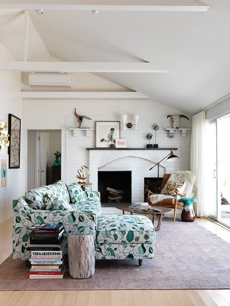 Chiếc ghế sofa họa tiết hoa lá xanh nhẹ nhàng đem tới màu xanh dịu mát cho căn phòng trắng.