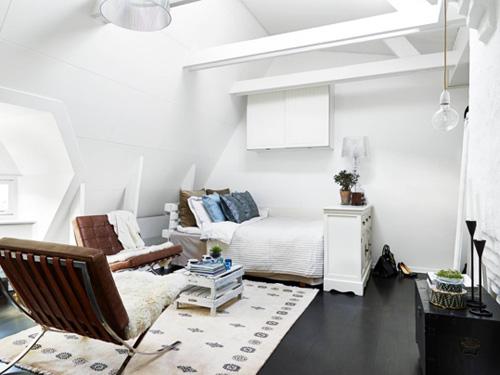 Căn hộ gác mái với nhiều nhược điểm như trần thấp, không vuông vắn được khắc phục với màu sơn trần, xà nhà, tường màu trắng.