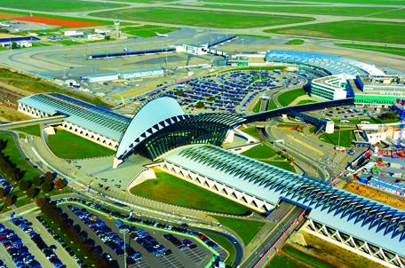 Tổng thể sân bay với khối sảnh cong kết nối trực tiếp với bãi đỗ ô tô và ga đường sắt ở 2 bên, Sân bay quốc tế Lyon-Saint Exupéry, Pháp