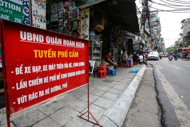 Bất chấp biển cấm buôn bán dưới lòng đường, hè phố ngay sát, nhiều cửa hàng vẫn ngang nhiên bày bàn ghế lấn chiếm vỉa hè. (Ảnh: Phú Quang/Vietnam+)