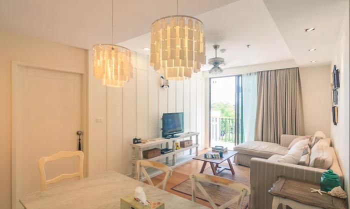 """Khi phòng khách và phòng ăn của bạn quá nhỏ, không đủ điều kiện để chia tách bằng một vách ngăn thực sự, bạn có thể tạo ra """"vách ngăn ảo"""" bằng đèn chùm hoặc thảm."""