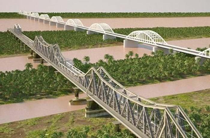 ĐSĐT trên cao đi bên cạnh ĐSQG, cả hai tuyến đường sắt vẫn cản trở đường bộ trong phố và không hỗ trợ bảo tồn cầu Long Biên. Nguồn : HanoidataST&BT