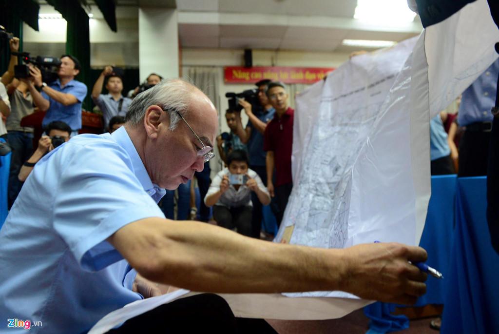 Ông Phan Nguyễn Như Khuê xem bản đồ Thủ Thiêm 1/10.000 do người dân trưng ra tại buổi tiếp xúc cử tri quận 2 vào ngày 9/5. Ảnh: Tùng Tin.