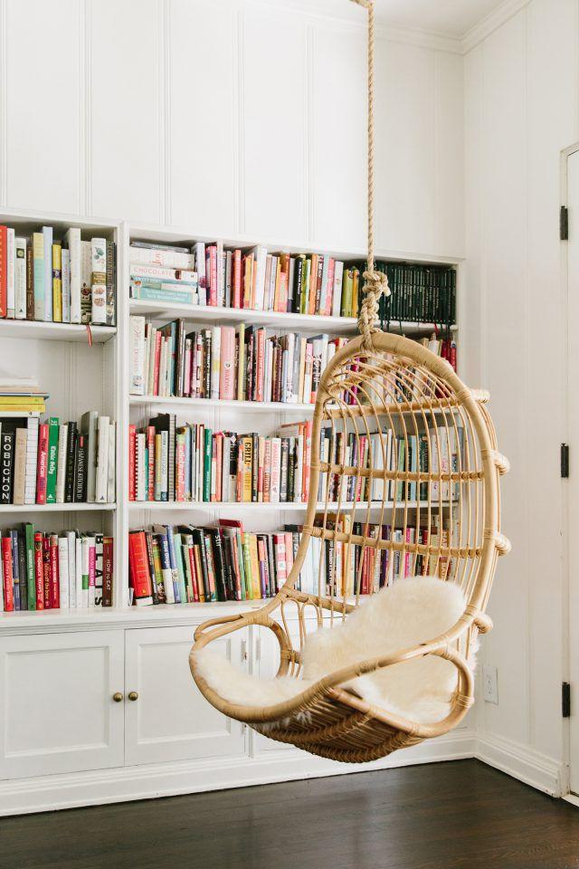 Một phong cách đầy ấn tượng cho không gian đọc sách với chiếc ghế treo, tủ sách chìm trong tường cùng màu sơn trắng tươi sáng.