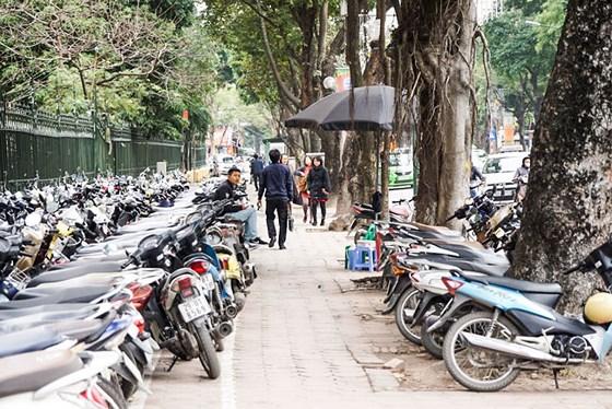 Vỉa hè dành cho người đi bộ cũng tận dụng làm bãi giữ xe máy. Ảnh: Viết Chung