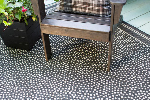 Chiếc ghế gỗ đúng màu nguyên bản, kết hợp với gối tựa, sàn nhà chấm bi là điểm nhấn thú vị khi làm mới hiên nhà bạn