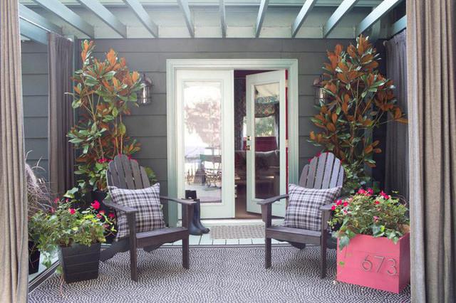 Trang trí hiên nhà với các chậu hoa là cách tạo ấn tượng tốt đẹp đầu tiên với khách đến chơi nhà. Những chiếc ghế gỗ mộc mạc kết hợp với gối tựa kẻ caro tạo nên phong cách Vintage nhẹ nhàng, độc đáo. Ngồi thưởng thức tách trà hay ly cà phê nóng hổi ngày thu se lạnh nơi hiên nhà này thì còn gì thú vị bằng.