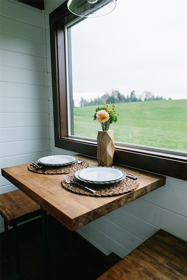 Khu vực ăn uống nhỏ và xinh bên cạnh cửa sổ có ghế gỗ cho hai người