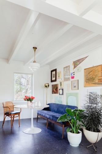 Nối tiếp phòng khách là không gian bàn trà và khu vực bếp, chủ nhà sử dụng sofa mềm và bàn tròn cùng với đèn phía trên để tạo cảm giác không quá cứng nhắc.