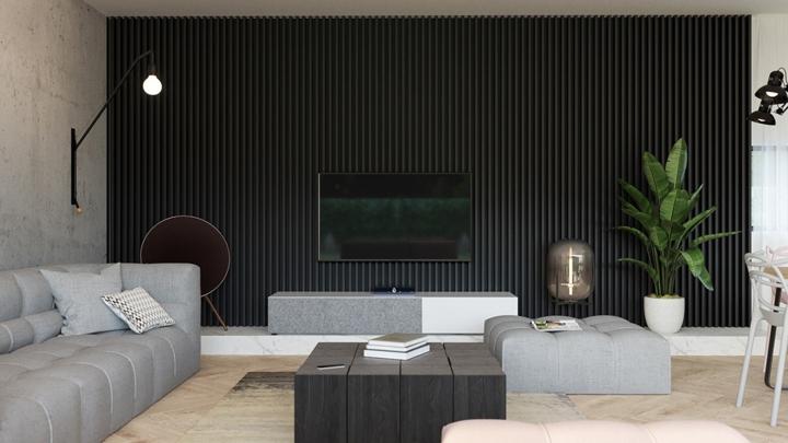 Đối diện với tường bê tông là bức tường đặt kệ tivi màu xám tối tăng thêm chiều sâu cho không gian