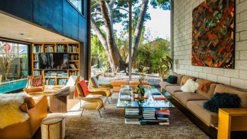 Ánh sáng từ khu vườn chiếu thẳng vào phòng khách có những đồ vật màu vàng và bức tranh rực rỡ treo trên tường