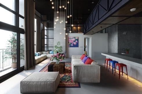 Chùm đèn hình tròn màu vàng treo trên trần nhà được chiếu thẳng xuống bộ bàn ghế sofa đã tạo nên nét lung linh huyền ảo cho căn phòng được thiết kế đơn giản