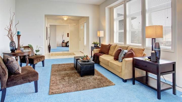 Không gian phòng khách như nối dài hơn với thảm trải lông đơn sắc