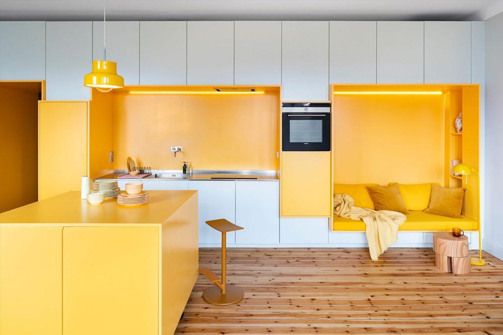 Căn phòng đa chức năng được phân khu bởi cách sắp đặt nội thất và màu sơn vàng - trắng. Một cột cố định lò nướng ngăn cách bồn rửa và góc đọc sách ấm cúng.