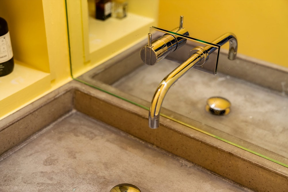 Bồn rửa bêtông màu xám thô tạo nên độ tương phản so với các nội thất màu vàng tươi sáng.