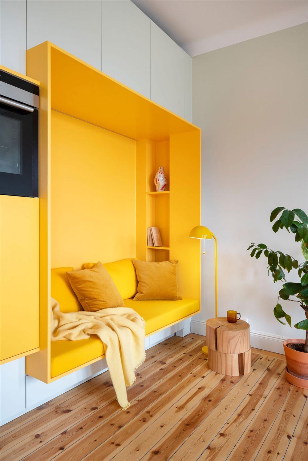 Kệ lõm đặt tài liệu và bình trang trí, chiếc bàn nhỏ bằng gỗ đặt đồ uống, và chiếc đèn sàn màu vàng cung cấp ánh sáng cho khu vực đọc sách. Tất cả mọi thứ bên trong khu vực này đều có màu vàng hoàn toàn.