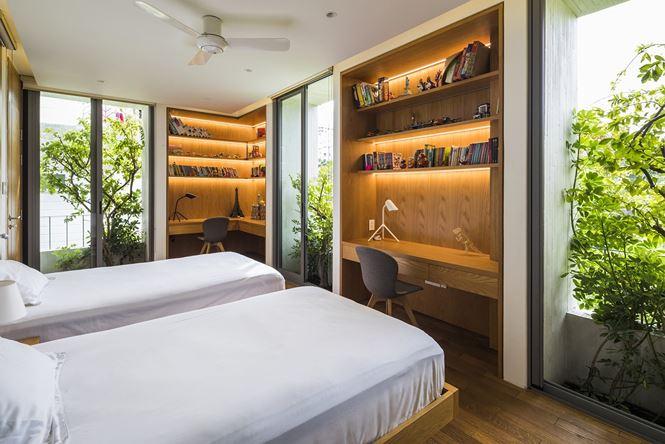 Phòng ngủ được thiết kế tinh tế với hai khu vực bàn học riêng biệt nhưng vẫn có sự gắn kết với cây cối