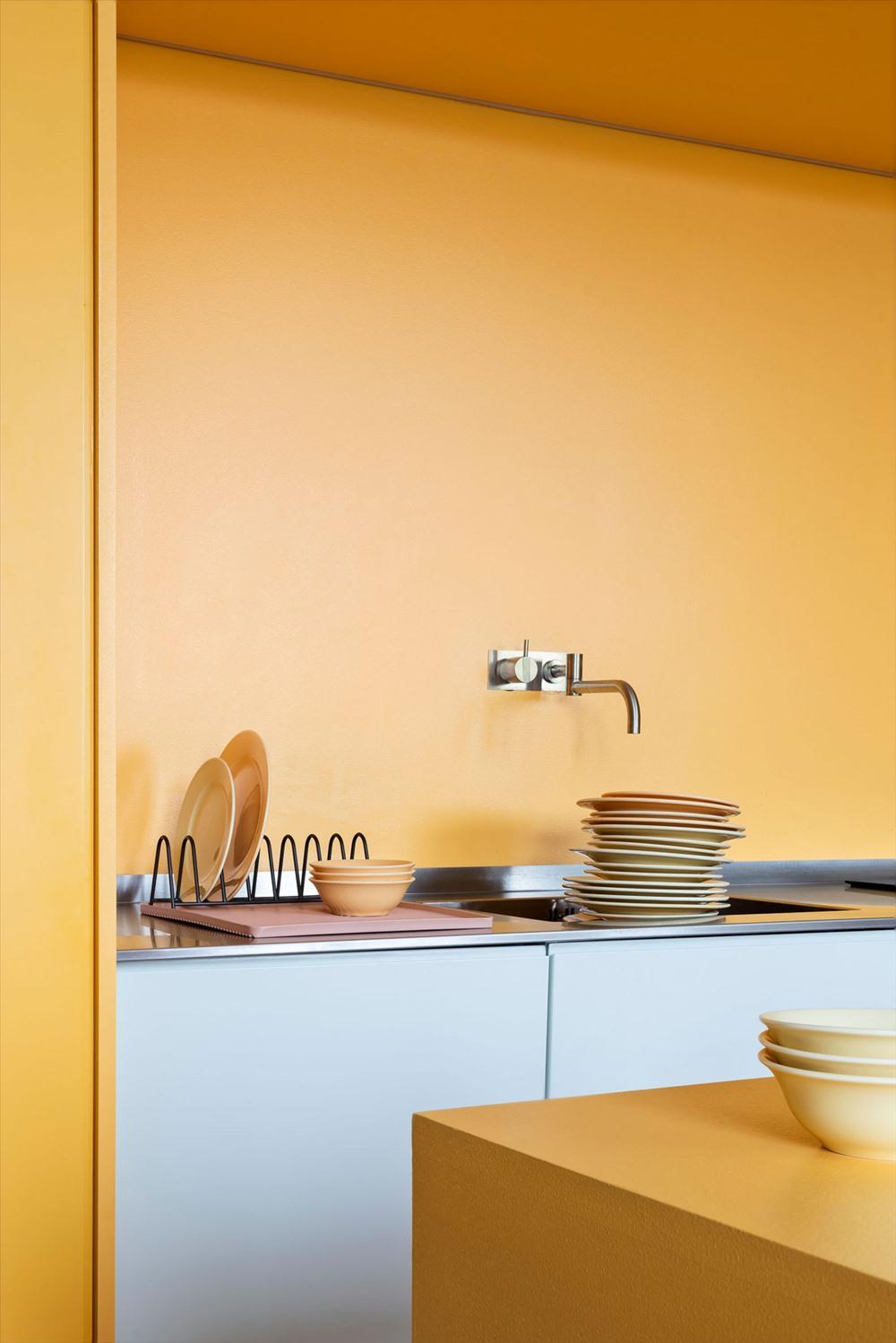Một vòi nước bằng thép không gỉ nhô ra từ một bức tường màu vàng. Cùng với đó là giá đỡ cũng bằng thép không gỉ góp phần trang trí nhà bếp sáng bóng.