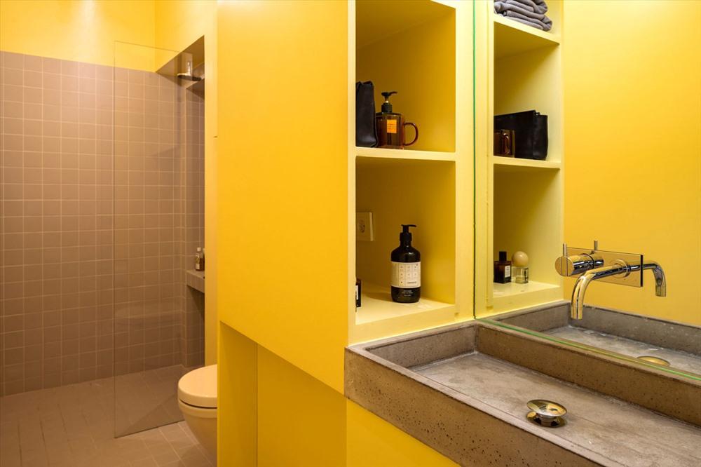 Kệ để đồ được xây nhằm ngăn cách giữa khu vực nhà vệ sinh và bàn trang điểm.