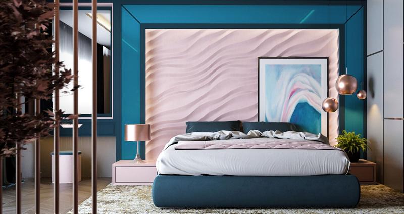Phòng ngủ mang phong cách hiện đại vì có bức tường màu hồng và xanh nổi vân như những viền cát gợn sóng. Ánh đèn ngủ rọi xuống tạo nên không gian lãng mạn cho căn phòng.