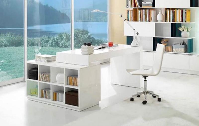 Kệ đựng sách và bàn làm việc màu trắng gắn liền nhau được đặt trong không gian làm việc thoáng mát, phía trước là cửa kính hướng ra ngoài có cảnh vật thiên nhiên