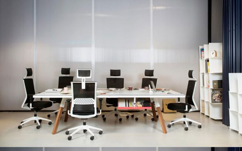 Bàn làm việc công sở rộng, quây xung quanh là những chiếc ghế cho nhiều người ngồi cùng trao đổi công việc
