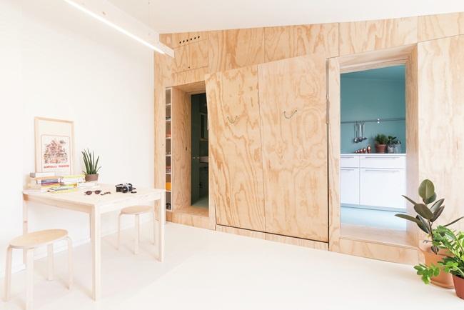 Hai bức tường ốp ván ép giúp che giấu đồ đạc, giường đôi, tủ quần áo, cửa trượt che nhà bếp và phòng tắm bên trong