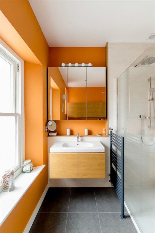 Sự góp mặt của gam màu cam tươi sáng giúp không gian phòng tắm bừng sức sống