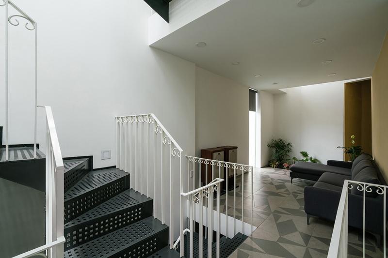 Ngoài khoảng thông tầng ở giữa nhà, cuối nhà còn một khoảng thông tầng khác giúp nắn lại thế đất góc cạnh. Thông tầng phía sau tiếp tục áp dụng phương pháp xiên, tăng hiệu quả thông gió, lấy sáng đồng thời thống nhất một tổng thể hình khối kiến trúc vươn về phía trước.