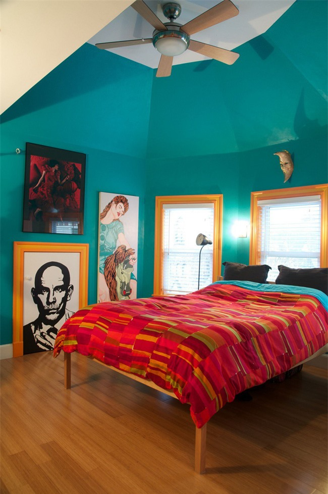 Một phòng ngủ màu ngọc lam được tạo điểm nhấn với bộ đồ giường màu đỏ và khung cửa sổ màu vàng sáng