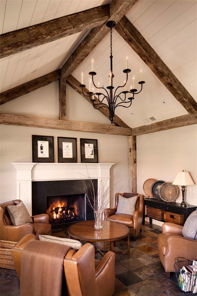 Phòng khách ấm áp với đồ nội thất bằng da màu nâu, tấm thảm màu ấm và dầm gỗ