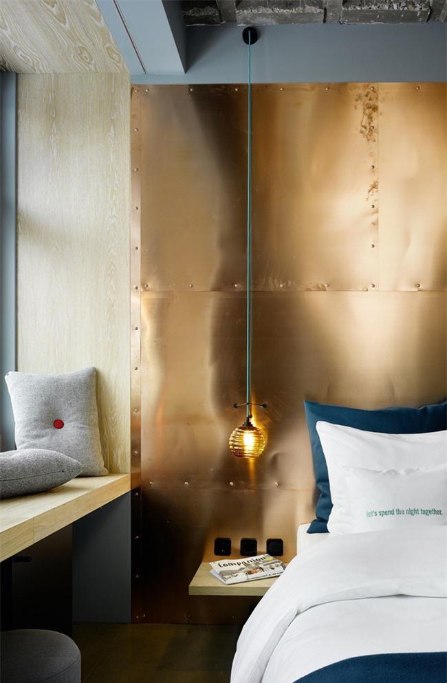Pha trộn màu sắc lạnh và ấm là một ý tưởng hoàn hảo. Ở đây một bức tường đồng được kết hợp với bộ đồ giường bằng ngọc lục bảo và gối màu xám