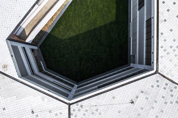 Mặt bằng hình chữ C bao bọc xung quanh một sân trung tâm, mở rộng về phía Nam nơi có một lối đi nhỏ ở tầng một.