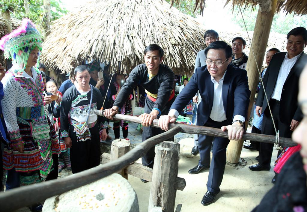 Phó Thủ tướng Vương Đình Huệ tham gia trải nghiệm xay gạo ở chợ người Mông, bản Sin Suối Hồ, Lai Châu. Ảnh: VGP
