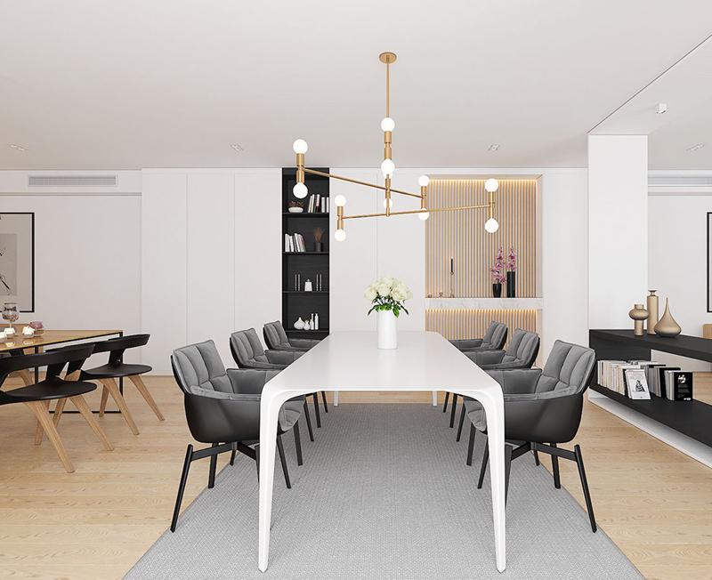 Ghế bọc nệm màu đen đặt cạnh bàn gỗ trắng, tạo sự tương phản ấn tượng.