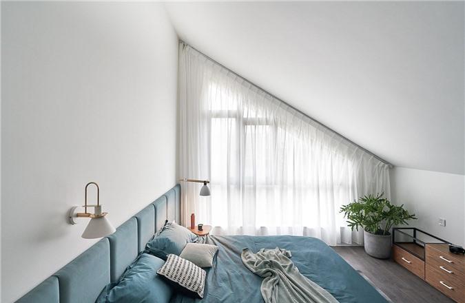 Màu xanh thêm độ sáng cho phòng ngủ màu trắng với trần nghiêng