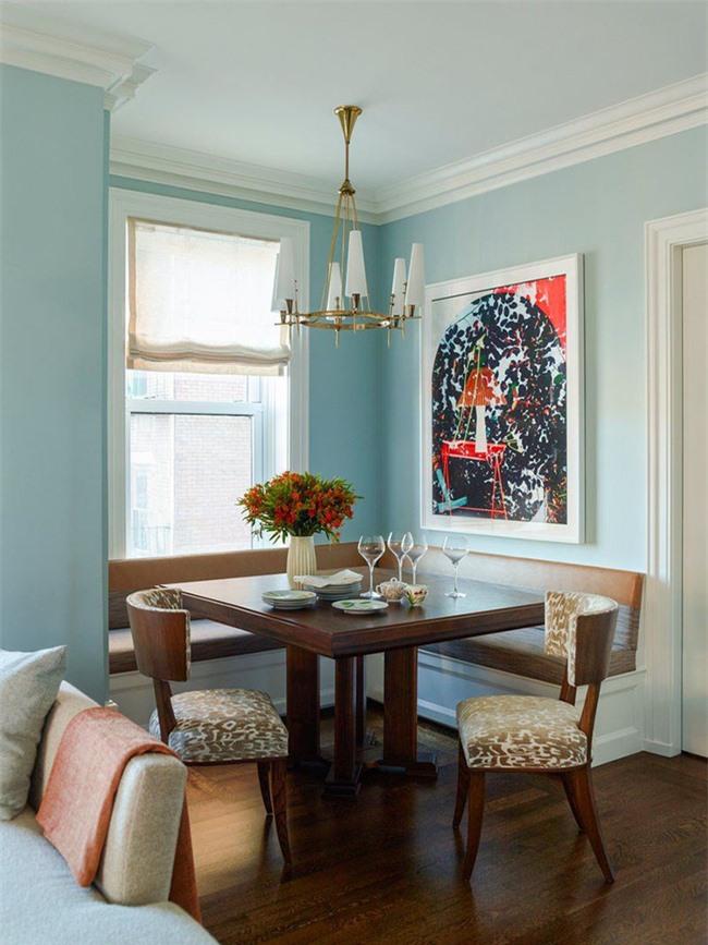 Bức tranh treo tường trông hoàn toàn nổi bật trên nền màu sắc trung tính của căn phòng ăn