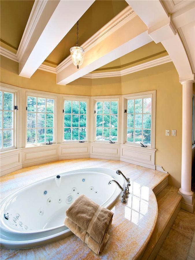 Phòng tắm lớn có rất nhiều cửa sổ và dầm trên trần nhà, với một bồn tắm hình bầu dục lớn cộng với một sàn đá xung quanh