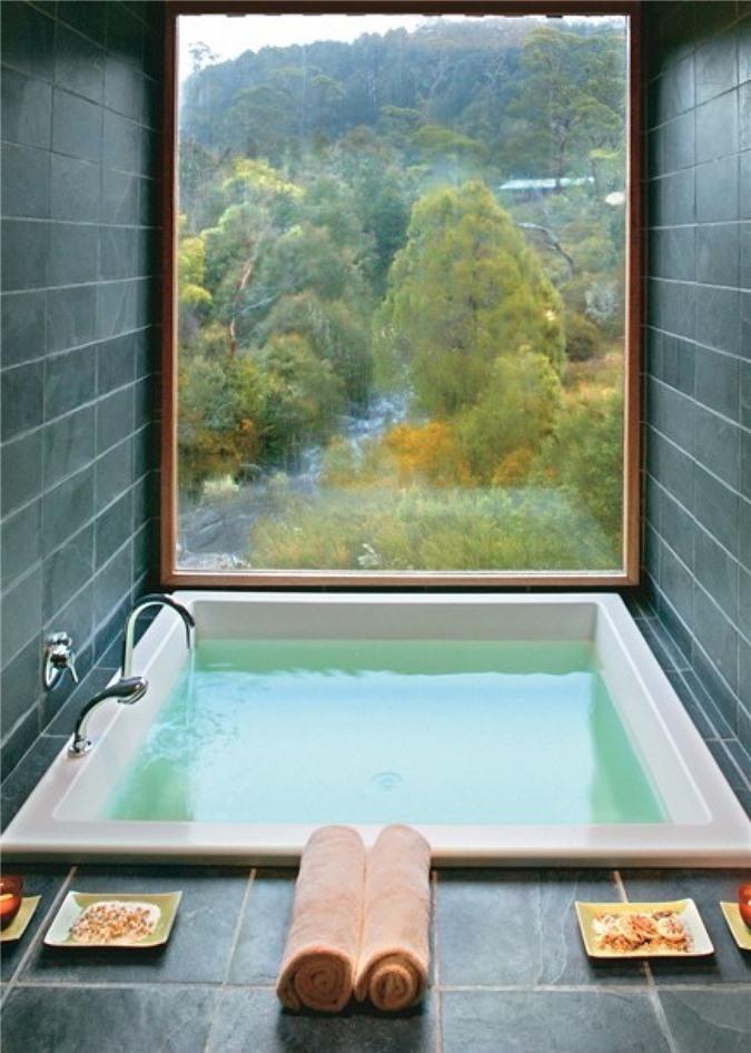 Phòng tắm lát gạch màu xám với cửa sổ toàn cảnh để ngắm cảnh và bồn tắm chìm để thư giãn hết mức có thể