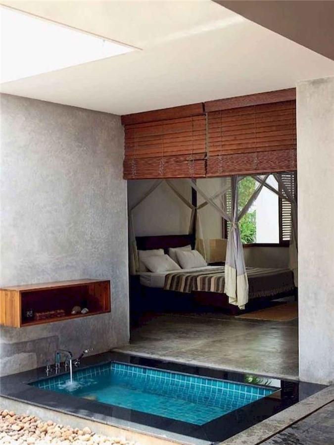 Bồn tắm chìm với gạch bên trong và đá xung quanh, với các sắc thái tách nó ra khỏi phòng ngủ