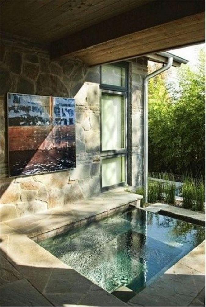 Phòng tắm ngoài trời trong nhà với bồn tắm chìm, được làm bằng đá và gạch cộng với ánh nắng mặt trời từ bên ngoài