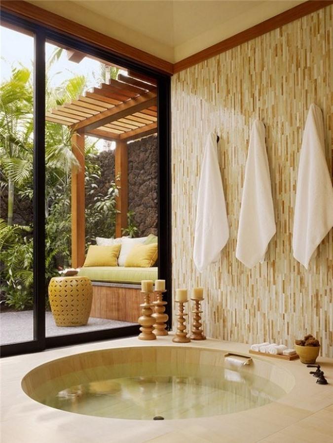 Phòng tắm nhiệt đới với gam màu trung tính với bồn tắm chìm và cửa trượt ra vườn để ngắm cảnh và đón nắng
