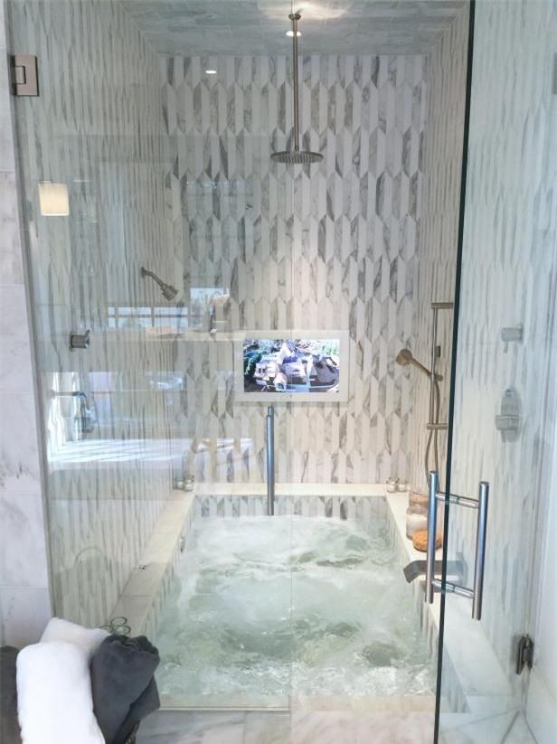 Bồn tắm chìm kết hợp với không gian tắm và ốp bằng gạch trung tính và bắt mắt rất thoải mái, tiết kiệm không gian