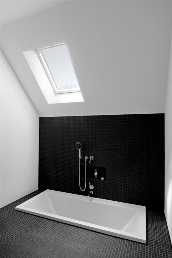 Phòng tắm đơn sắc tối thiểu với hai màu đen và trắng, có giếng trời và bồn tắm chìm là một không gian rất đơn giản và phong cách
