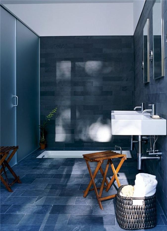Phòng tắm màu hải quân và màu xám với một bồn tắm chìm và bồn rửa màu trắng cộng với ghế đẩu bằng gỗ cùng giỏ để lưu trữ